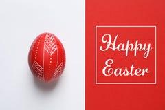Páscoa feliz pintada vermelha do ovo e do texto no fundo da cor foto de stock royalty free