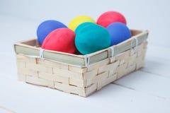 Páscoa, feriados, tradição e conceito do objeto - próximo acima de ovos da páscoa coloridos na cesta Imagens de Stock Royalty Free