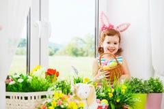 Páscoa menina feliz da criança com orelhas do coelho e o sitti colorido dos ovos imagem de stock