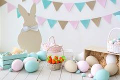 Páscoa! Muitos ovos da páscoa coloridos com coelhos e cestas! Decoração da sala, a sala da Páscoa de crianças para jogos Cesta co imagens de stock