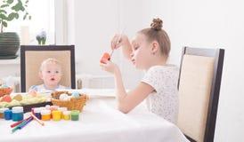 Páscoa no círculo de família: Uma menina pinta um ovo da páscoa Os relógios mais novos da irmã com entusiasmo imagens de stock