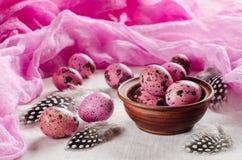 Páscoa Os ovos cor-de-rosa minúsculos e as penas bonitas Imagem de Stock