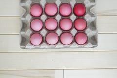 Páscoa Os ovos da páscoa cor-de-rosa estão no suporte de ovo A vista da parte superior Máscaras pasteis do rosa Fotografia de Stock