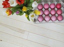 Páscoa Os ovos da páscoa e as tulipas cor-de-rosa encontram-se em um fundo de madeira Configuração lisa Foto de Stock