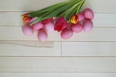 Páscoa Os ovos da páscoa e as tulipas cor-de-rosa encontram-se em um fundo de madeira Configuração lisa Fotografia de Stock