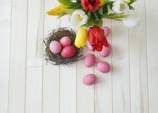 Páscoa Os ovos da páscoa e as tulipas cor-de-rosa encontram-se em um fundo de madeira Configuração lisa Imagem de Stock Royalty Free