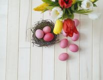 Páscoa Os ovos da páscoa e as tulipas cor-de-rosa encontram-se em um fundo de madeira Configuração lisa Imagens de Stock Royalty Free
