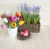 Páscoa Os ovos da páscoa e as tulipas cor-de-rosa encontram-se em um fundo de madeira Configuração lisa Fotografia de Stock Royalty Free