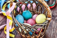 Páscoa Ovos da páscoa em uma cesta e em umas fitas coloridas Fotografia de Stock
