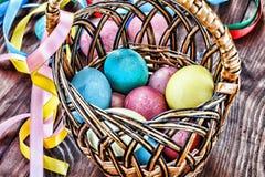 Páscoa Ovos da páscoa em uma cesta e em umas fitas coloridas Imagem de Stock