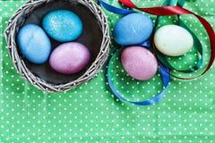 Páscoa Ovos da páscoa em uma cesta em um fundo verde e em umas fitas coloridas Easter feliz Foto de Stock