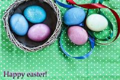 Páscoa Ovos da páscoa em uma cesta em um fundo verde e em umas fitas coloridas Easter feliz Fotos de Stock