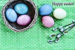 Páscoa Ovos da páscoa em uma cesta em um fundo verde e em umas fitas coloridas Easter feliz Imagens de Stock