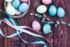 Páscoa Ovos da páscoa em uma cesta, em umas fitas coloridas e em uns ramos do salgueiro, vista superior Imagens de Stock Royalty Free
