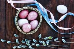 Páscoa Ovos da páscoa em uma cesta, em umas fitas coloridas e em uns ramos do salgueiro, vista superior Fotos de Stock