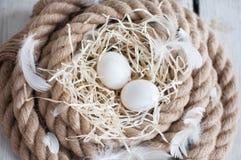 A Páscoa, ovos, galinha eggs, ovos de codorniz, ovos, corda, ninho, branco, penas, no feno Foto de Stock