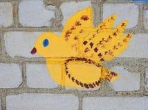 Pássaro amarelo pintado na parede velha, Lituânia foto de stock royalty free
