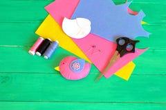 Pássaro de feltro, linhas e uma agulha, folhas do feltro, pinos, tesouras, moldes de papel - grupo da costura Como fazer o brinqu imagem de stock royalty free