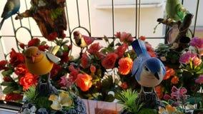 Pássaro do brinquedo e as flores artificiais Fotografia de Stock