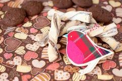 Pássaro e cookies vermelhos do brinquedo no guardanapo escuro com imagem dos corações Fotografia de Stock