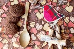 Pássaro e cookies vermelhos do brinquedo no guardanapo escuro com imagem dos corações Fotos de Stock Royalty Free