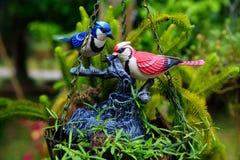 Pássaros cerâmicos coloridos em potenciômetros de flor de suspensão Imagem de Stock
