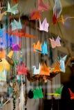 Pássaros de papel coloridos do origâmi amarrados às cordas Imagem de Stock