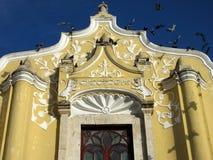 Pássaros e igreja Católica amarela imagem de stock