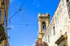 Pássaros que voam acima de uma torre de sino medieval da igreja em Rabat, Malta Fotos de Stock