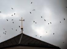 Pássaros que voam em torno de uma cruz da igreja Fotos de Stock Royalty Free