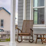 Pátio de entrada coberto quadrado de uma casa com as cadeiras de balanço marrons e as colunas brancas retangulares fotografia de stock