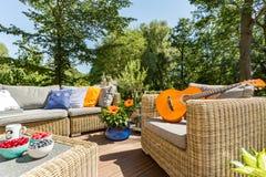 Pátio do verão com mobília e guitarra do rattan fotos de stock