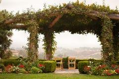 Pátio e cadeiras cobertos videira com opinião do país Foto de Stock Royalty Free