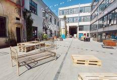 Pátio na parte urbana da cidade com galerias artísticas e os bancos estranhos ao redor Fotografia de Stock Royalty Free