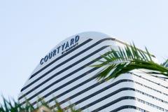 Pátio pelo sinal de Marriott, no quadro das folhas de palmeira Fachada do hotel de luxo imagem de stock royalty free