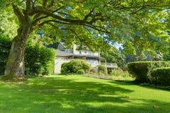 Pátio traseiro autêntico do grande verão verde com a grande casa marrom cinzenta fotografia de stock
