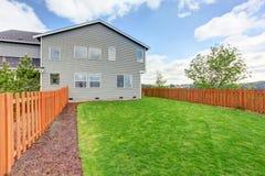 Pátio traseiro cercado espaçoso com grama verde Exterior da casa de uma grande casa imagem de stock royalty free
