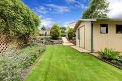 Pátio traseiro com passagem da grama, barraca de jardinagem pequena, e mergulhado Fotos de Stock