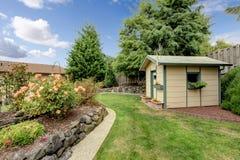 Pátio traseiro com passagem da grama, barraca de jardinagem pequena, e mergulhado Imagens de Stock Royalty Free
