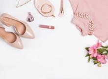 Pâle - accessoires et fleurs féminins roses sur le fond blanc photographie stock libre de droits