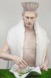 Pâlissez l'homme blond dans l'équipement blanc mangeant de la nourriture biologique Photographie stock libre de droits