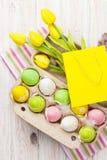 Pâques avec les tulipes jaunes, les oeufs colorés et le cadeau mettent en sac Photos stock