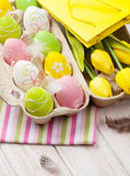 Pâques avec les tulipes jaunes, les oeufs colorés et le cadeau mettent en sac Photo stock