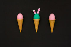 Pâques a coloré des oeufs dans des cônes de gaufre sur un fond noir Photo stock