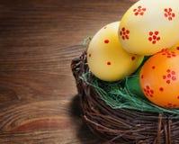 Pâques a coloré des oeufs dans le nid image stock