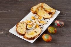 Pâques a coloré des oeufs et a coupé en tranches le pain de Pâques dans le plat blanc sur le conseil en bois gris Image stock