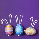 Pâques a coloré des oeufs sur le lilas un fond, avec les oreilles peintes de lièvres Fond pour une carte postale, concept de Pâqu Images libres de droits