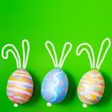 Pâques a coloré des oeufs sur le vert un fond, avec les oreilles peintes de lièvres Fond pour une carte postale, concept de Pâque Photo libre de droits