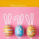 Pâques a coloré des oeufs sur un fond rose, avec les oreilles peintes de lièvres Fond pour une carte postale, concept de Pâques,  Photographie stock libre de droits