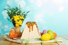 Pâques curds le dessert, les oeufs colorés, les fleurs et les papillons sur a Photos stock